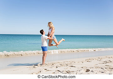 Happy couple jumping on beach vacations - Travel concept of...