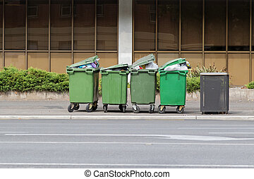 Over filled Wheelie bins, waste containers full of trash on...