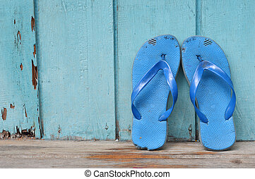 old used blue flip-flops on wooden wall