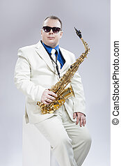 Music Concept and Ideas. Handsome Caucasian Musician With Alto Saxophone Posing In White Suit and Black Sunglasses Against White Background.