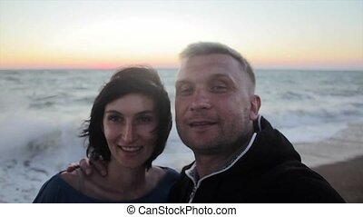 Happy couple taking selfie on beach at sunset using phone