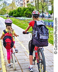 Girls wearing helmet and rucksack ciclyng bicycle. - Bikes...