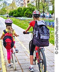 Girls wearing helmet and rucksack ciclyng bicycle. - Bikes...