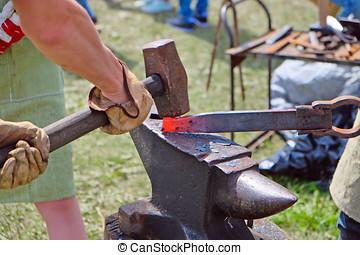 hammer forging hot iron at anvil