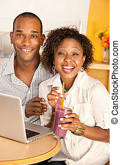 Couple on a Laptop - Young couple smile as they work on a...