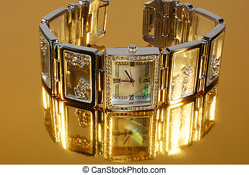 Woman brand watch on gold background with reflection
