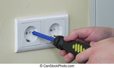 closeup of electrician hands with screwdriver unscrew outlet...