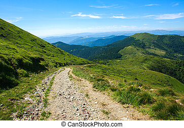 Soil road in mountains on background blue sky in summer