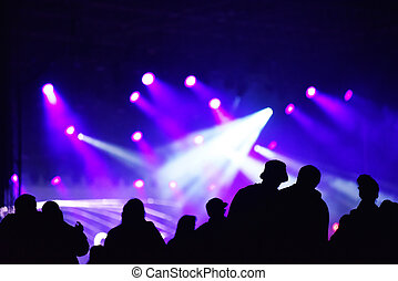 Silhouette of cheering crowd at a concert. Colourful bright stage lights in the background