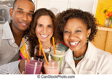 Friends Socializing Over Smoothies - A group of friends are...