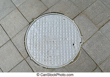 Grey metal cover of the hatch covering the technology pit to underground utilities