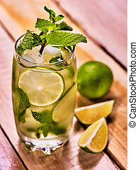 On wooden boards is glass with mohito and lime. - On wooden...