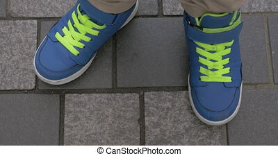 Kid feet in blue trainers on paved sidewalk - Top close-up...