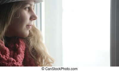 Pretty casual woman standing at window, wearing hat