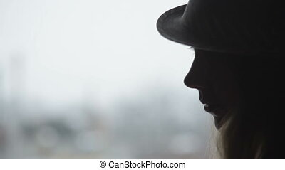 Pretty casual woman standing at window, wearing hat, looking...