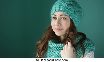 beautiful young woman in a turquoise knitted hat and scarf.