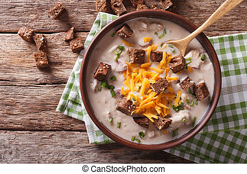 Bavarian beer soup with cheese and bacon close up in a bowl....