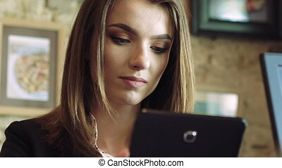 Woman using a tablet, speaking in cafe. Look through coffee...