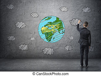 Businessman drawing the Earth and clouds in colour on the concrete wall