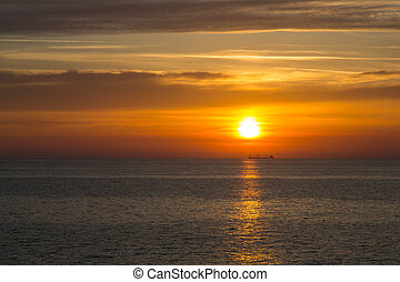 Sunset at sea with boat on horizon