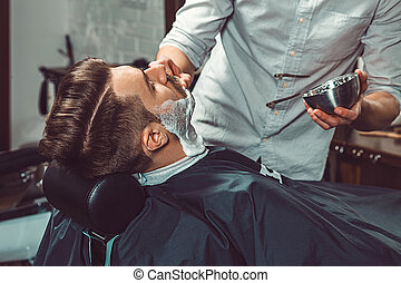 Hipster client visiting barber shop The hands of young...