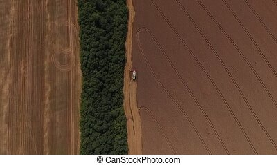 harvester threshing wheat aerial shoot.