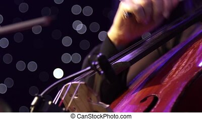 Concert, a musician pinching the strings cello, fingers...