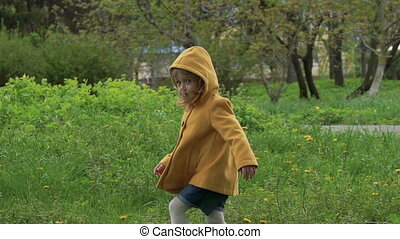 Little girl walking on the grass in the park. Slowly
