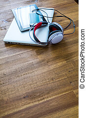 Digital devices and Headphones on a wooden Desktop - A...