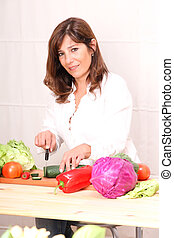 Cooking - A beautiful mature woman cutting vegetables in the...