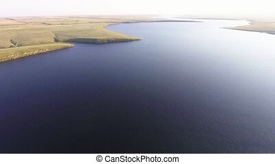 Flying over the big river. Aerial view from copter.