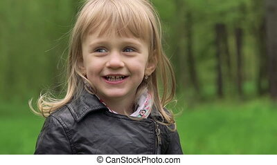 Cute little blond girl smiling in a park. Slowly.