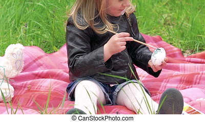 Baby girl painting egg on a lawn and smiling on camera. Slowly