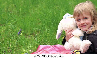 Little girl's playing with soft toy on a lawn in a park.