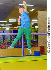 Exuberant young boy bouncing on a trampoline punching at the...