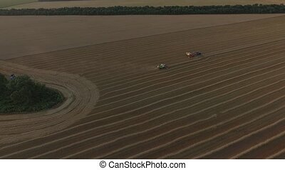 Combaines harvesters and truck on wheat field aerial view