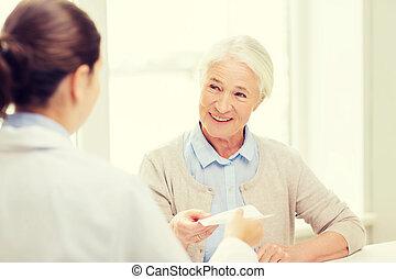 doctor giving prescription to senior woman