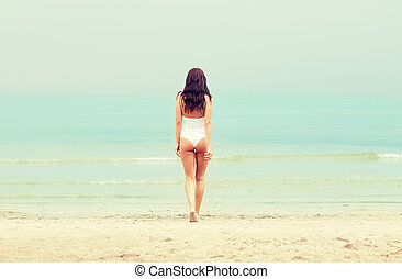 young woman in swimsuit walking on beach - summer vacation,...