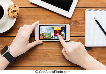 close up of woman with smartphone on wooden table -...