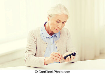 senior woman with glucometer checking blood sugar -...