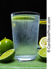 Glass with cold sparkling mineral water with fresh lime -...