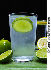 Glass with cold sparkling mineral water, lime and lemon,...