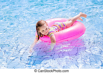 Child in swimming pool - Happy little girl playing with...