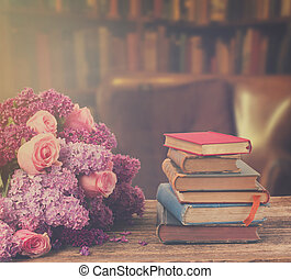 Bookshelf with flowers - Wooden bookshelf with stack of...