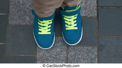 Child feet in blue trainers on sidewalk - Top close-up shot...