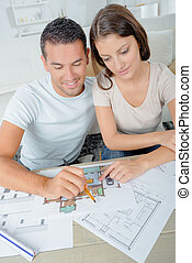 Couple looking over plans for their new home
