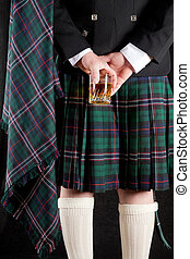 Whisky and kilt - Scotsman holding his glass of whisky...