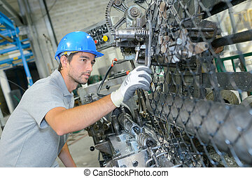 Factory worker adjusting machine with wrench