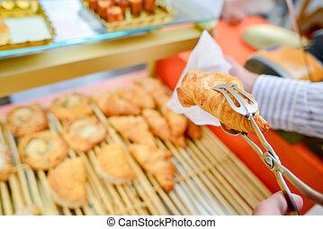 Croissant held in tongs