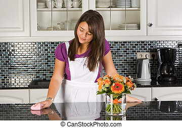 Dreaming in the kitchen - Young woman cleaning the kitchen...